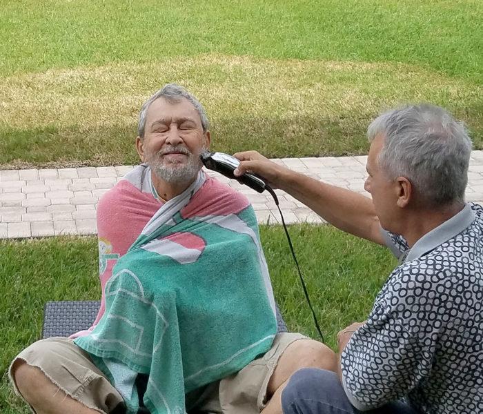 man trimming a other mans beard