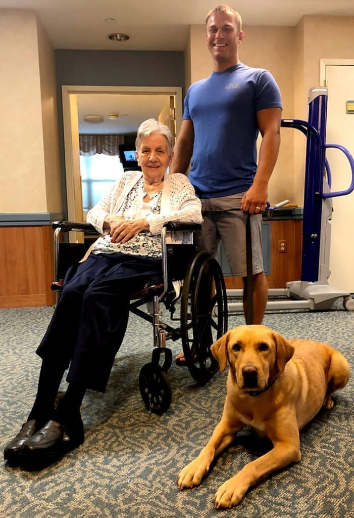 lady sitting on a wheel chair dog sitting beside lady and a man standing before lady