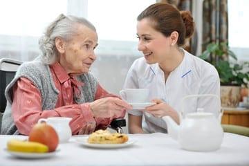 caregiver having tea with an elderly patient